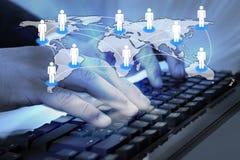 Uomo d'affari che scrive sulla tastiera di computer con la mappa di mondo collegata Immagine Stock