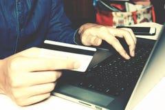 Uomo d'affari che scrive sulla tastiera e che tiene carta con il onli di acquisto Fotografia Stock Libera da Diritti