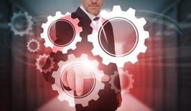 Uomo d'affari che seleziona l'interfaccia futuristica della ruota e del dente Fotografia Stock
