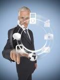 Uomo d'affari che seleziona un ologramma con le applicazioni dello smartphone Fotografie Stock