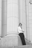 Uomo d'affari che si appoggia contro la colonna Immagine Stock Libera da Diritti