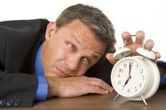 Uomo d'affari che si appoggia sull'orologio di sorveglianza dello scrittorio Immagine Stock