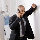 Uomo d'affari che si appoggia sulla parete che comunica sul telefono delle cellule Immagini Stock