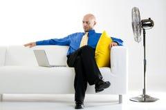 Uomo d'affari che si distende con il ventilatore fotografie stock