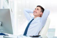 Uomo d'affari che si distende nell'ufficio Immagine Stock