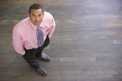 Uomo d'affari che si leva in piedi all'interno Fotografia Stock Libera da Diritti