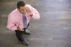 Uomo d'affari che si leva in piedi all'interno per mezzo del telefono cellulare Fotografie Stock Libere da Diritti