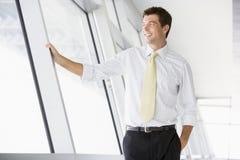 Uomo d'affari che si leva in piedi nel sorridere del corridoio Fotografia Stock