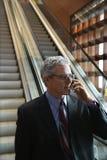 Uomo d'affari che si leva in piedi sulla scala mobile. Immagini Stock
