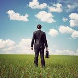 Uomo d'affari che si leva in piedi in un campo fotografie stock