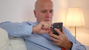 Uomo d'affari che si rilassa nelle notizie finanziarie leggenti del cellulare di uso dell'ufficio su Internet archivi video
