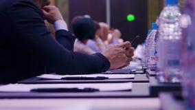 Uomo d'affari che si siede ad una tavola e che tiene una penna azione Uomo d'affari con una penna alla conferenza video d archivio