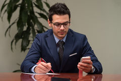 Uomo d'affari che si siede alla scrivania che firma un contratto Immagini Stock Libere da Diritti