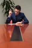Uomo d'affari che si siede alla scrivania che firma un contratto Immagine Stock Libera da Diritti