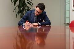 Uomo d'affari che si siede alla scrivania che firma un contratto Fotografie Stock