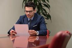 Uomo d'affari che si siede alla scrivania che firma un contratto Fotografia Stock