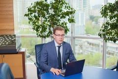 Uomo d'affari che si siede alla tabella Immagini Stock