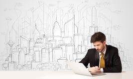 Uomo d'affari che si siede alla tavola bianca con le costruzioni disegnate a mano Fotografia Stock