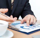 Uomo d'affari che si siede alla tavola con i documenti Immagini Stock