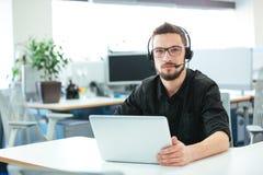 Uomo d'affari che si siede allo scrittorio con il computer portatile Fotografia Stock Libera da Diritti