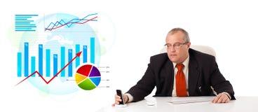 Uomo d'affari che si siede allo scrittorio con le statistiche Fotografie Stock
