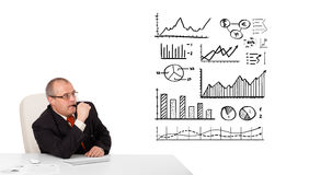 Uomo d'affari che si siede allo scrittorio con le statistiche ed i grafici immagine stock