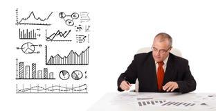 Uomo d'affari che si siede allo scrittorio con le statistiche ed i grafici fotografia stock libera da diritti