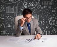 Uomo d'affari che si siede allo scrittorio con lo schema e le icone di affari Fotografie Stock Libere da Diritti