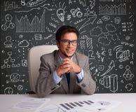 Uomo d'affari che si siede allo scrittorio con lo schema e le icone di affari Immagine Stock