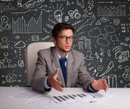 Uomo d'affari che si siede allo scrittorio con lo schema e le icone di affari Fotografia Stock