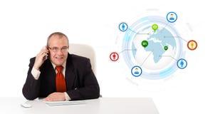 Uomo d'affari che si siede allo scrittorio e che fa una telefonata con il globo a Immagini Stock