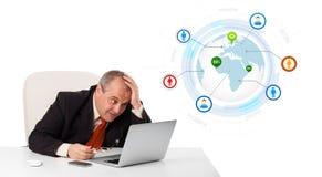 Uomo d'affari che si siede allo scrittorio e che guarda computer portatile con il globo e così Immagini Stock Libere da Diritti