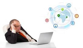 Uomo d'affari che si siede allo scrittorio e che guarda computer portatile con il globo e così Fotografia Stock Libera da Diritti