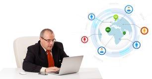 Uomo d'affari che si siede allo scrittorio e che guarda computer portatile con il globo e così Immagini Stock