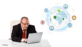 Uomo d'affari che si siede allo scrittorio e che guarda computer portatile con il globo e così Immagine Stock