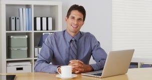 Uomo d'affari che si siede allo scrittorio e che parla con macchina fotografica con il computer portatile Fotografie Stock