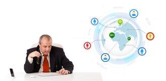 Uomo d'affari che si siede allo scrittorio e che scrive sulla tastiera con il globo Fotografia Stock