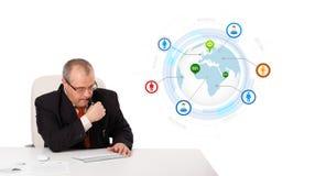 Uomo d'affari che si siede allo scrittorio e che scrive sulla tastiera con il globo Immagine Stock Libera da Diritti