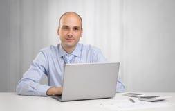 Uomo d'affari che si siede allo scrittorio in ufficio Fotografie Stock Libere da Diritti