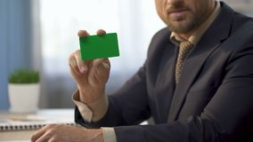 Uomo d'affari che si siede allo scrittorio in ufficio, mostrante la carta colorata di verde, servizi del credito stock footage