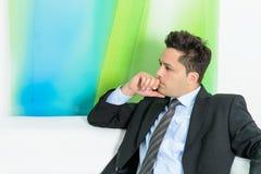 Uomo d'affari che si siede allo strato Immagini Stock