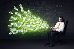Uomo d'affari che si siede in compressa della tenuta della sedia con le banconote in dollari co Fotografia Stock