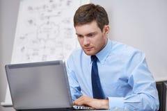 Uomo d'affari che si siede con il computer portatile in ufficio Immagini Stock