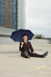 Uomo d'affari che si siede con l'ombrello Fotografia Stock Libera da Diritti