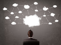 Uomo d'affari che si siede con la tecnologia della nuvola sopra la sua testa Fotografie Stock Libere da Diritti