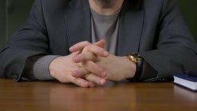 Uomo d'affari che si siede con le dita attraversate Uomo d'affari che si siede alla tavola con le dita attraversate stock footage