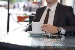 Uomo d'affari che si siede con una tazza di caffè e un telefono ad una tavola nera con una riflessione immagini stock