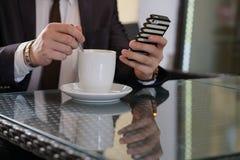 Uomo d'affari che si siede con una tazza di caffè e un telefono ad una tavola nera con una riflessione fotografia stock