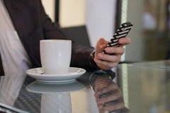 Uomo d'affari che si siede con una tazza di caffè e un telefono ad una tavola nera con una riflessione fotografie stock libere da diritti