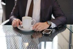 Uomo d'affari che si siede con una tazza di caffè e un telefono ad una tavola nera con una riflessione fotografie stock